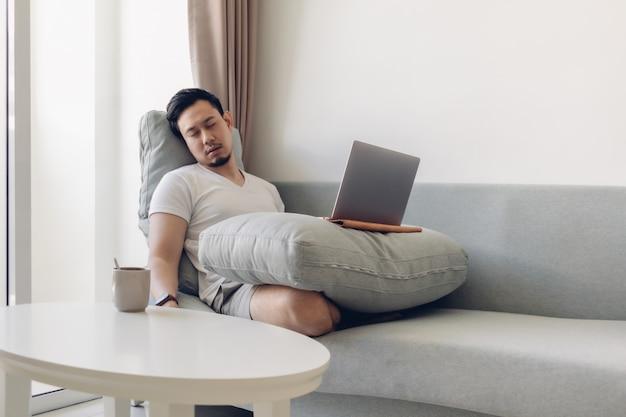 Uomo asiatico assonnato che lavora al suo computer portatile sul divano.