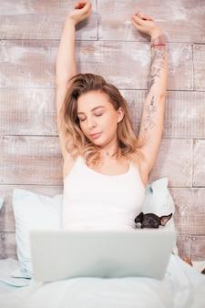 Bella donna assonnata in pigiama di notte che si allunga mentre si lavora al computer portatile.