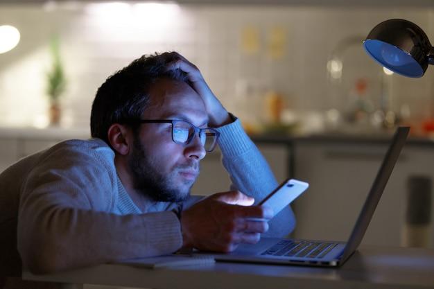 Progettista annoiato sonnolento dell'uomo in occhiali facendo uso dello smartphone a casa di notte