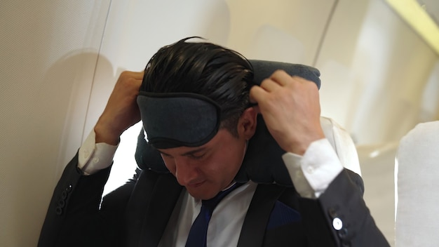 Uomo d'affari assonnato viaggio in viaggio d'affari in aereo. concetto di viaggiatore esecutivo.