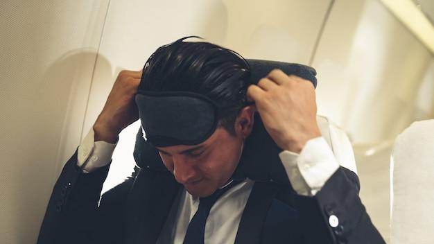 Uomo d'affari assonnato viaggio in viaggio d'affari in aereo