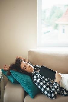 Donna caucasica sonnolenta con capelli ricci che riposa sul divano dopo aver letto un libro