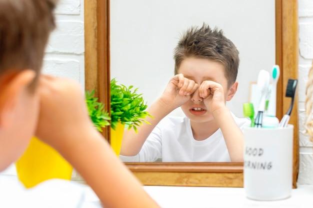 Bambino assonnato in pigiama sta davanti allo specchio e si strofina gli occhi con le mani in bagno la mattina presto. il bambino si è appena svegliato e vuole dormire, cattivo umore, routine mattutina.