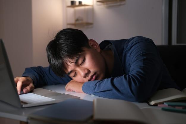 Giovane collage esausto assonnato che fa gli straordinari alla scrivania in ufficio con il suo laptop, sta per addormentarsi, privazione del sonno e concetto di lavoro straordinario.