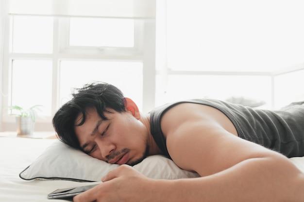 L'uomo assonnato sta usando lo smartphone sdraiato sul letto.