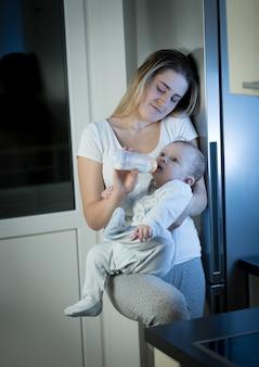 Madre assonnata che allatta il figlio del bambino dalla bottiglia in cucina di notte