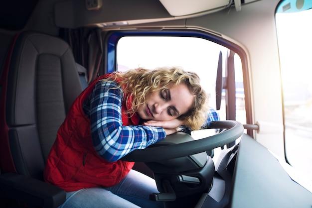 Autista di camion femminile assonnato e stanco che dorme sul volante all'interno della cabina del veicolo del camion.