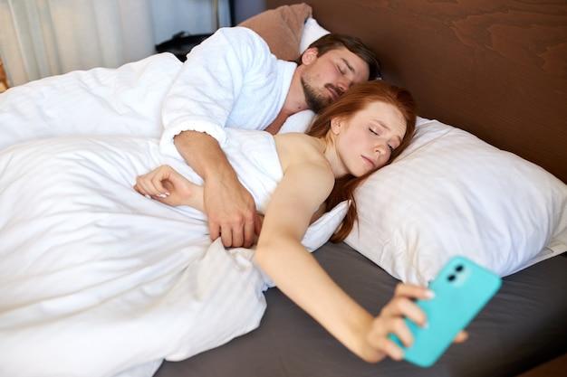 La donna assonnata sta controllando l'orologio nel telefono, è ora di svegliarsi