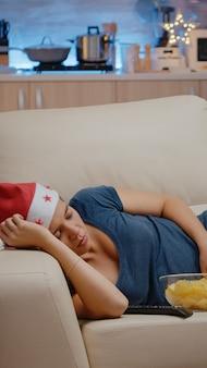 Donna assonnata che indossa un cappello da babbo natale e si riposa sul divano