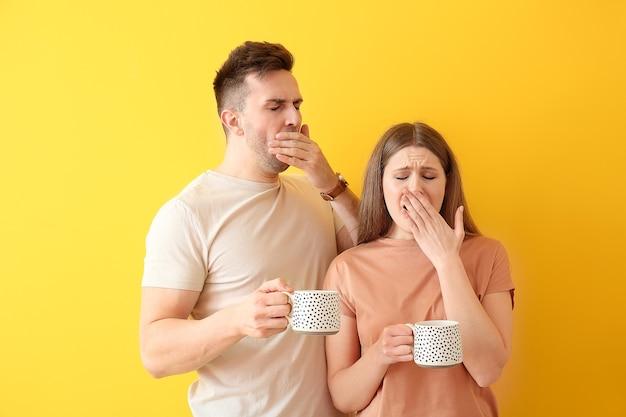 Giovane coppia assonnata con caffè sul colore
