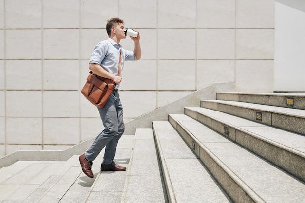 Giovane imprenditore assonnato che sale le scale quando si affretta a lavorare e beve caffè da asporto