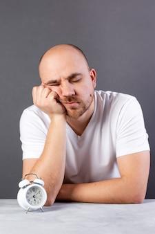Giovane sonnolento su sfondo grigio con sveglia