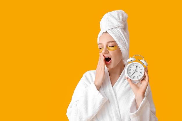 Giovane donna sonnolenta con sveglia sulla superficie di colore