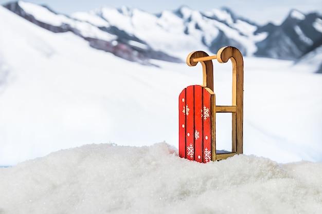 Slitta in un cumulo di neve di fronte a montagne innevate inverno natale superficie