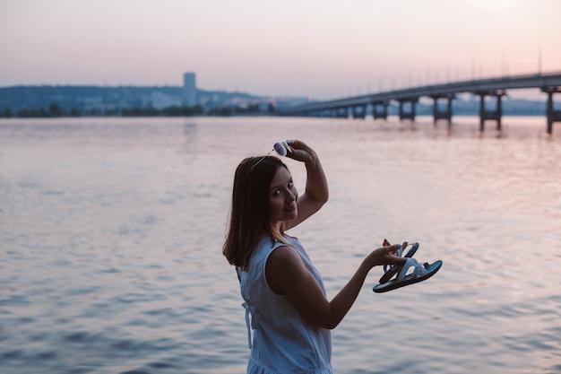 Una donna bruna snella sta mezzo girata si toglie gli occhiali da sole al tramonto con vista sulla cit...