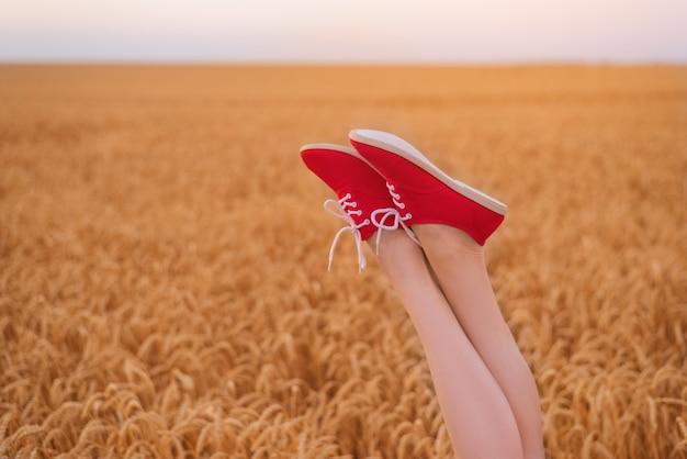 Piedini femminili snelli in scarpe da ginnastica rosse sul campo di sfondo di grano maturo. avvicinamento.