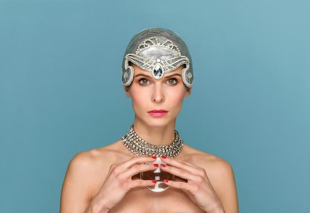 Modello femminile snello in tiara d'argento alla moda e con sfera di vetro in studio sull'azzurro che guarda l'obbiettivo