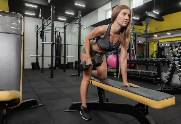 Una donna snella che pratica il sollevamento di manubri in pendenza in palestra. uno stile di vita sano. bodybuilding e fitness