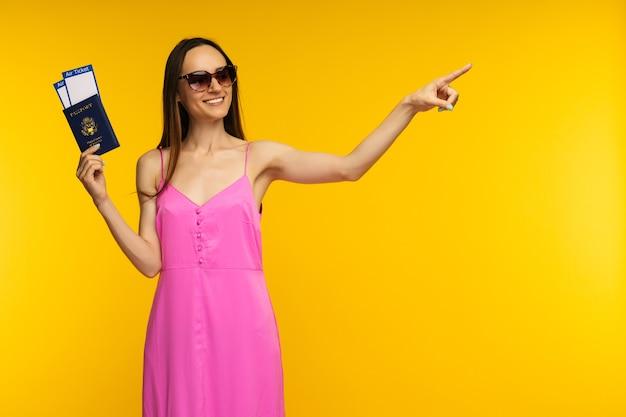 Ragazza snella in un vestito rosa e occhiali da sole in possesso di passaporto con biglietto aereo