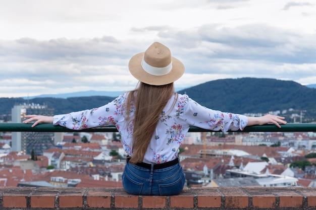 Una ragazza snella con i capelli lunghi in un cappello si siede sul bordo di un edificio alto e guarda la città di graz.