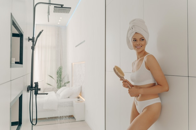 Modello femminile snello felice in posa con la testa avvolta in un asciugamano appoggiato al muro del bagno e tenendo una spazzola di legno, preparandosi per la doccia mattutina e la routine igienica. bellezza e cura del corpo delle donne