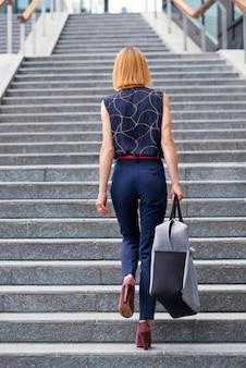Donna snella ed elegante che cammina su una rampa di scale esterne in città portando una grande borsa o valigia alla moda in una vista posteriore a tutta lunghezza con copyspace