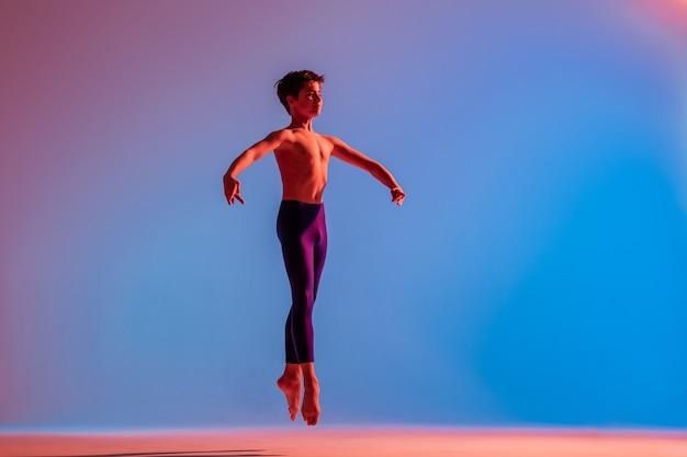 Il ragazzo di balletto teenager snello salta a piedi nudi sotto la luce colorata.