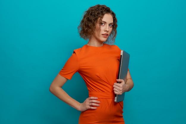 Donna snella in vestito arancione che tiene computer portatile.