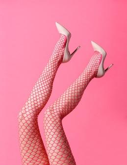Donna snella che indossa calze a rete rosa sexy e tacchi a spillo in posa con i piedi in su