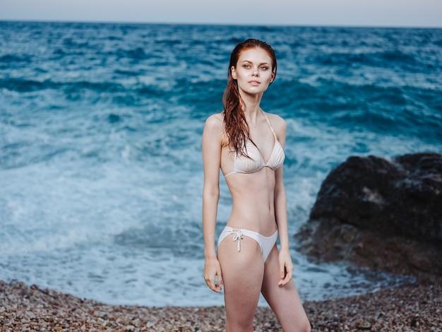 Una donna snella in un costume da bagno bianco gesticola con le mani sulla riva dell'oceano.