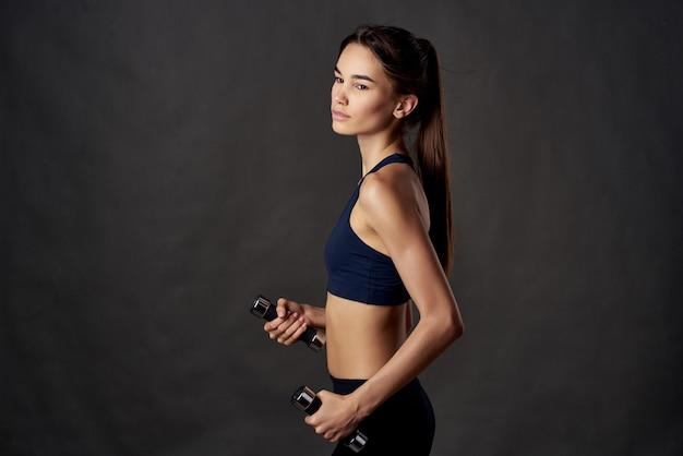 Donna snella con manubri in mano con esercizi di allenamento palestra studio