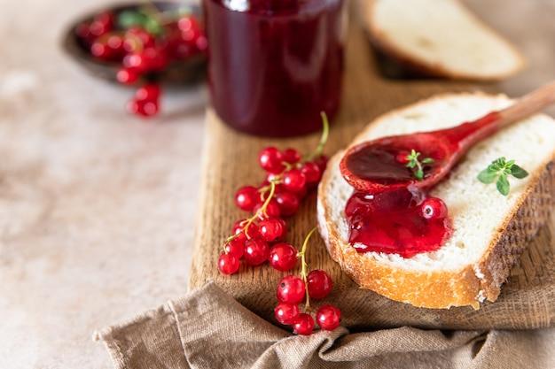 Fetta di pane e marmellata di ribes rosso o gelatina in un cucchiaio, tagliere di legno. messa a fuoco selettiva.