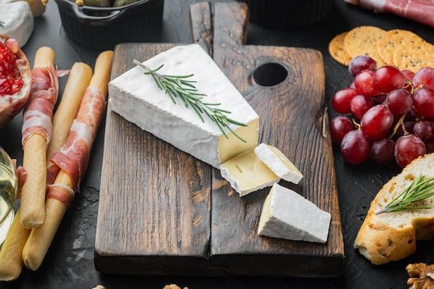Fetta di brie fattoria cremoso formaggio morbido insieme, sulla tavola nera
