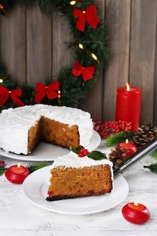 Fetta di torta ricoperta di crema con decorazioni natalizie sul tavolo, su parete in legno