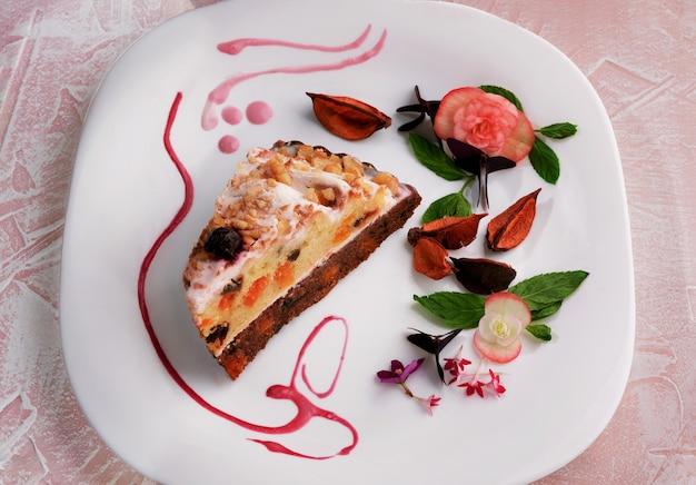 Fetta di torta di formaggio con frutta secca decorata sulla zolla bianca.