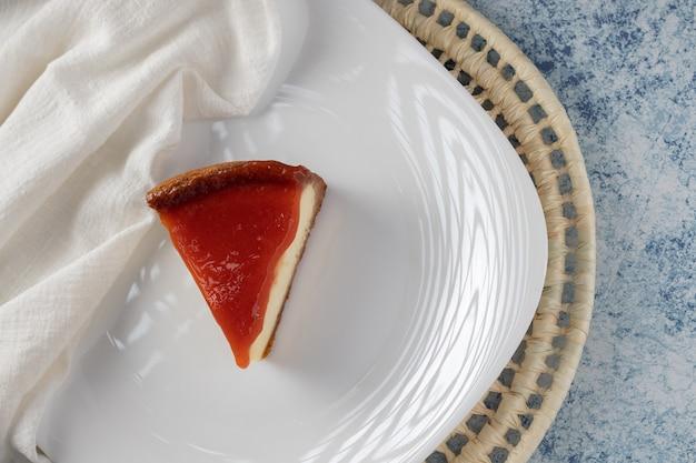Fetta di cheesecake con pasta di guava su un piatto bianco su sfondo grigio e blu. vista dall'alto