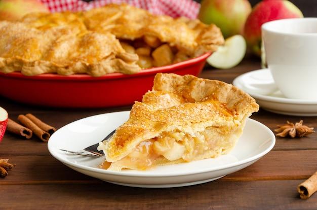 Fetta di torta di mele americana classica con cannella su un piatto bianco