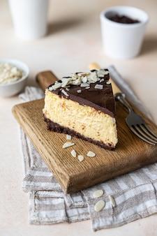 Fetta di cheesecake cremosa con glassa al cioccolato e mandorle
