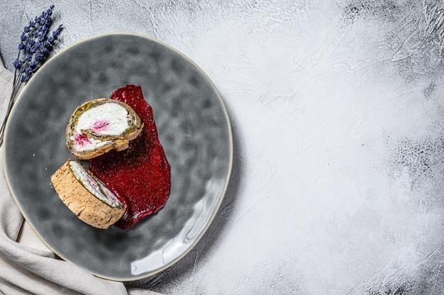Fetta di rotolo di dessert con marmellata di fragole e crema. sfondo grigio. vista dall'alto. copia spazio