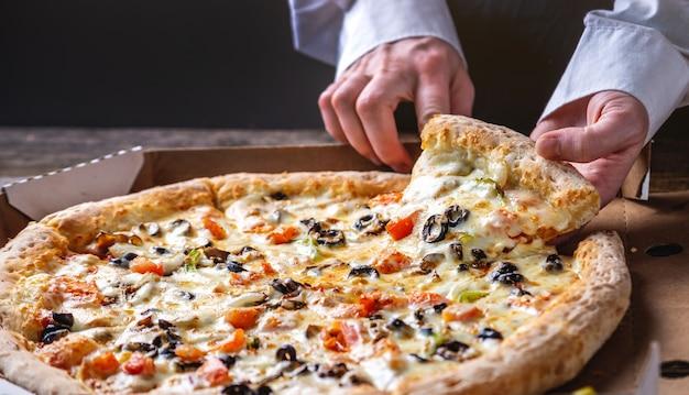 Una fetta di pizza vegetariana fresca calda con una striscia di mozzarella in mano al cuoco.