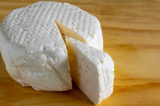Fetta di formaggio bianco fresco di miniera sulla tavola di legno.