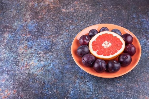Fetta di pompelmo con deliziose prugne poste in un piatto arancione.