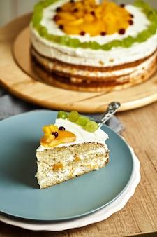 Fetta di torta al caramello fatta in casa con frutta sulla piastra. fondo in legno