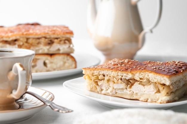 Una fetta di pollo fatto in casa e torta di sesamo su un piatto bianco vicino a una caffettiera e una tazza di caffè sfondo bianco primo piano