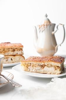 Una fetta di pollo fatto in casa e torta di sesamo. su un piatto bianco. vicino a una caffettiera e una tazza di caffè. sfondo bianco.