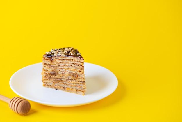 Una fetta di torta frittella fatta in casa con noci caramellate al cioccolato e miele su una parete gialla