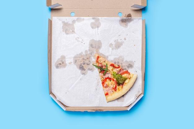 Fetta di pizza fresca calda si trova in un pacchetto di cartone su un blu