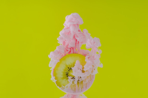 Affetta il kiwi con il fuoco parziale di dissoluzione del colore rosa del manifesto in acqua