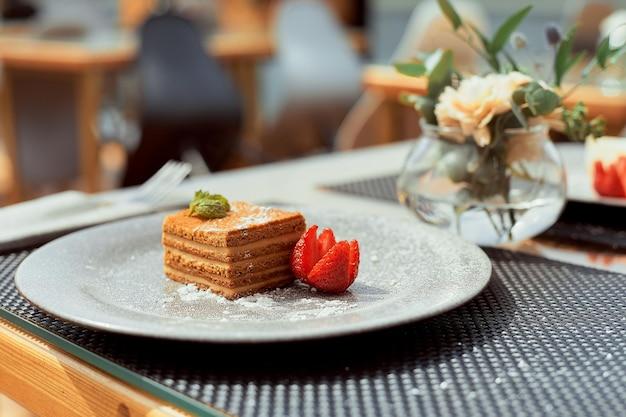 Fetta di torta di miele a strati medovik russo decorato con menta e mandorle su piatto bianco.