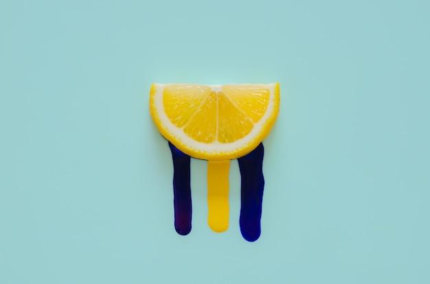 Affetta il limone che ha il colore del poster giallo e blu scuro che cade da esso. minimo concetto estivo.